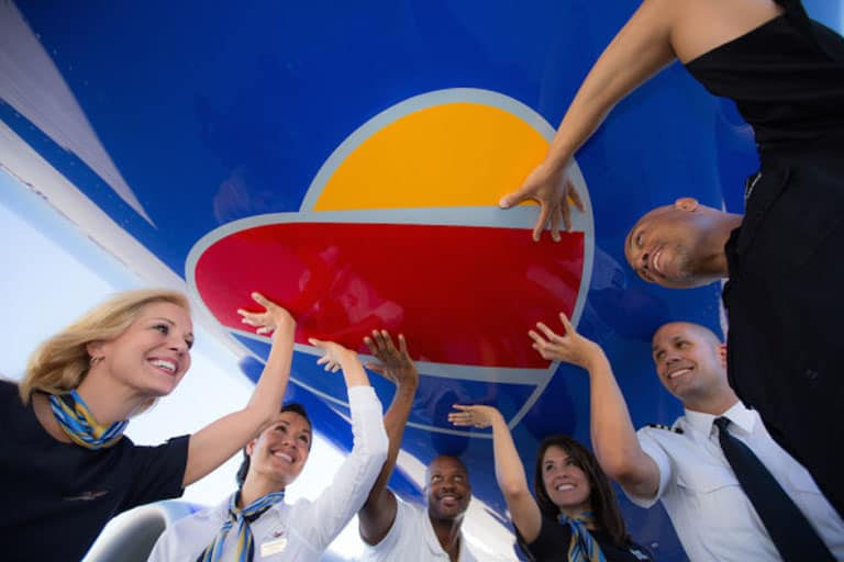 employees of southwest airlines touching the company logo