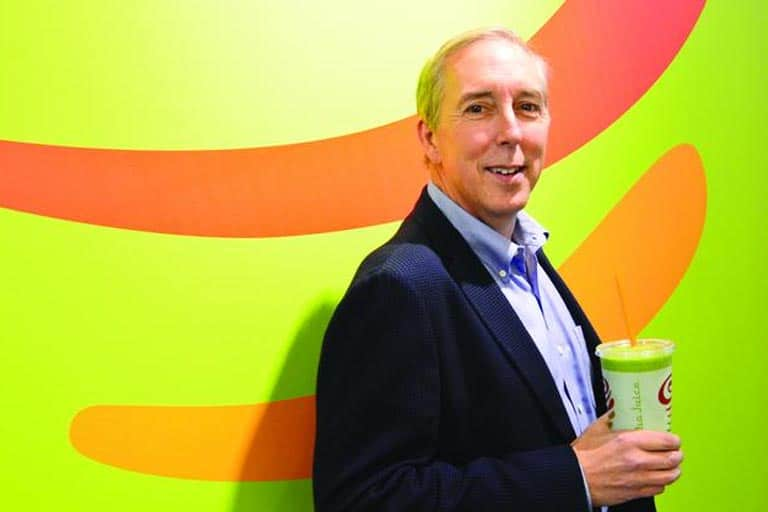 corporate man in suit  holding a cup of jamba juice