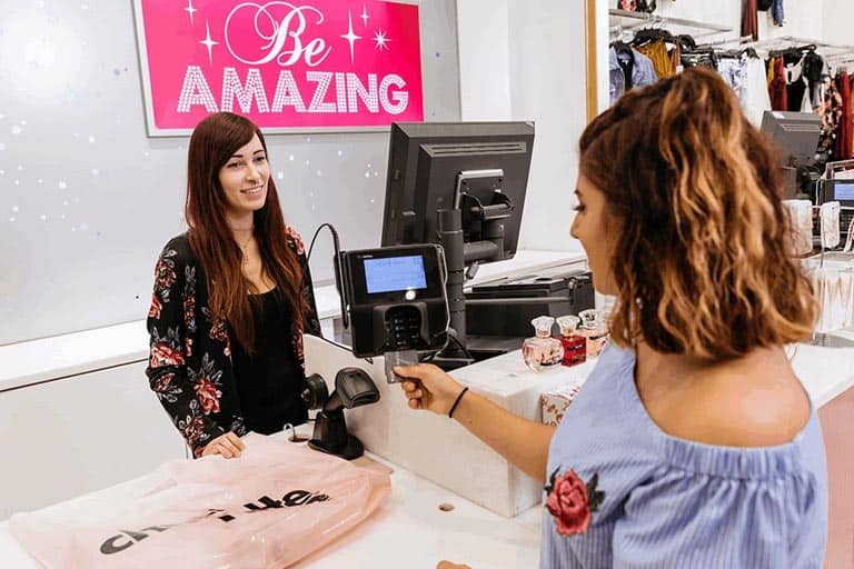 customer paying through her credit card at the cashier of charlotte russe store