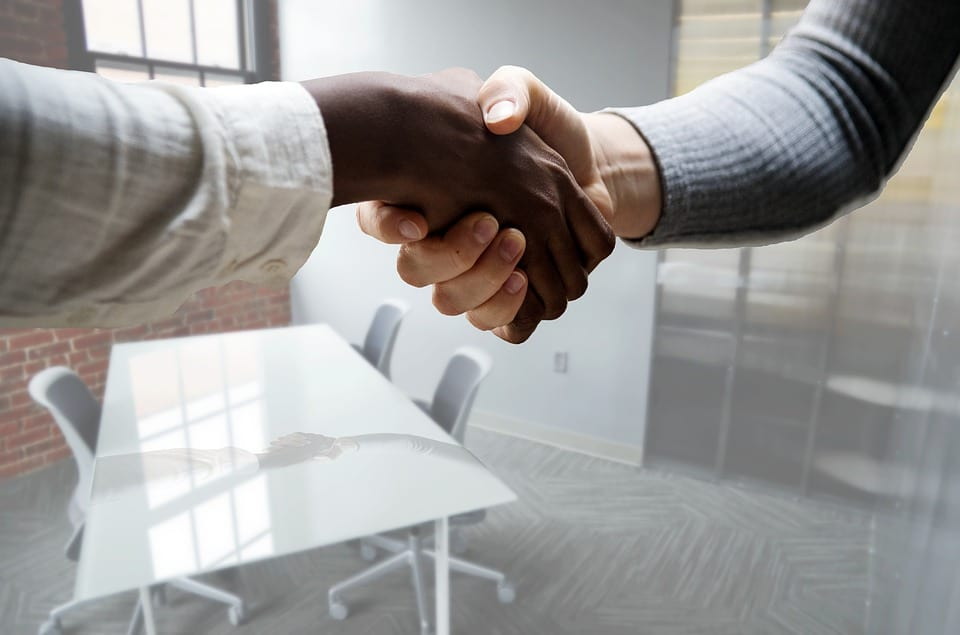 two persons shaking hands after an interview session